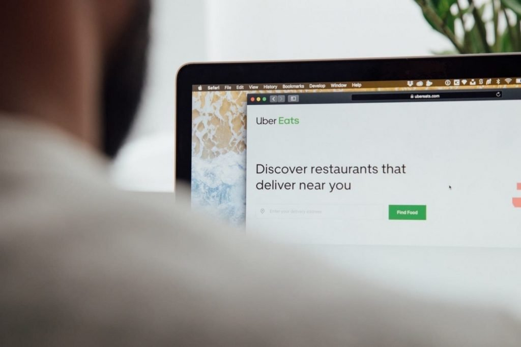 Person looking for a restaurant online. Consumer shopping trends are seeing an uptick in delivery during the time of COVID-19.