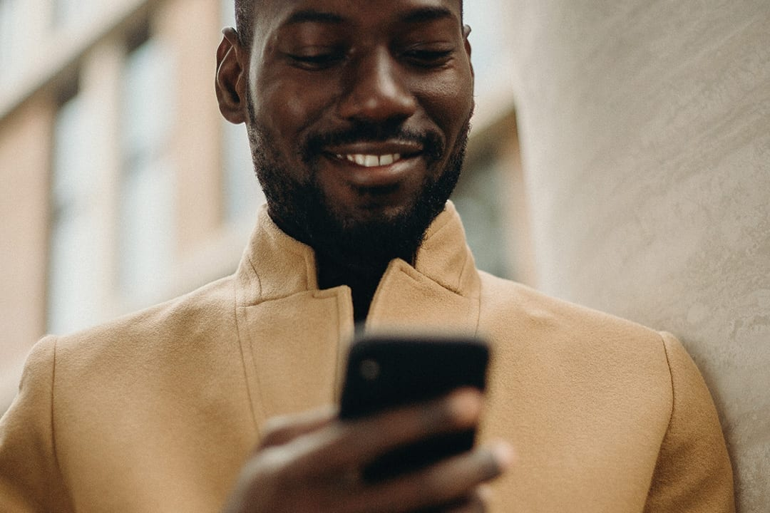Smiling man using a mobile phone.